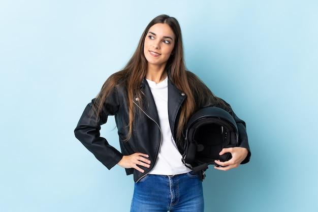 젊은 여자 엉덩이에 팔을 포즈와 미소 파란색 벽에 고립 된 오토바이 헬멧을 들고