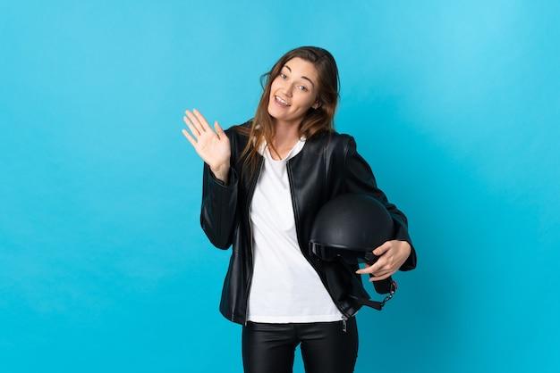 幸せな表情で手で敬礼青い壁に分離されたオートバイのヘルメットを保持している若い女性