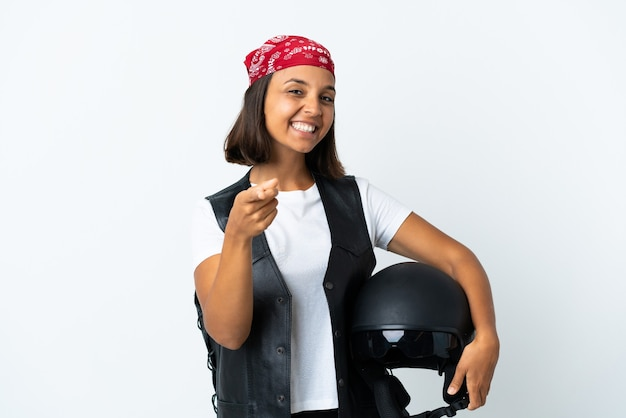 幸せな表情で白いポインティングフロントに分離されたオートバイのヘルメットを保持している若い女性