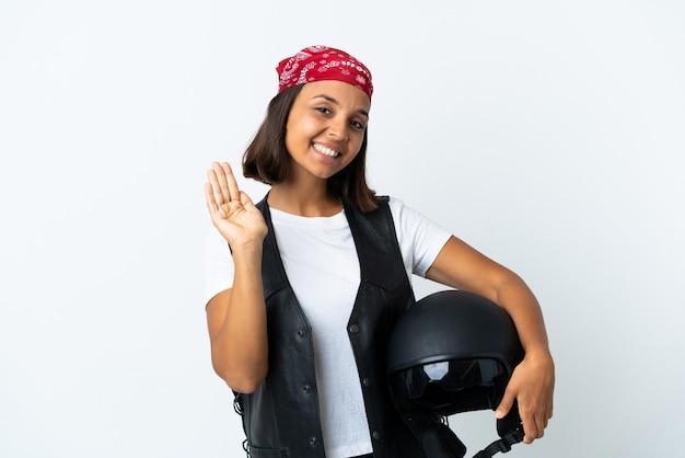幸せな表情で手で敬礼白で隔離のオートバイのヘルメットを保持している若い女性