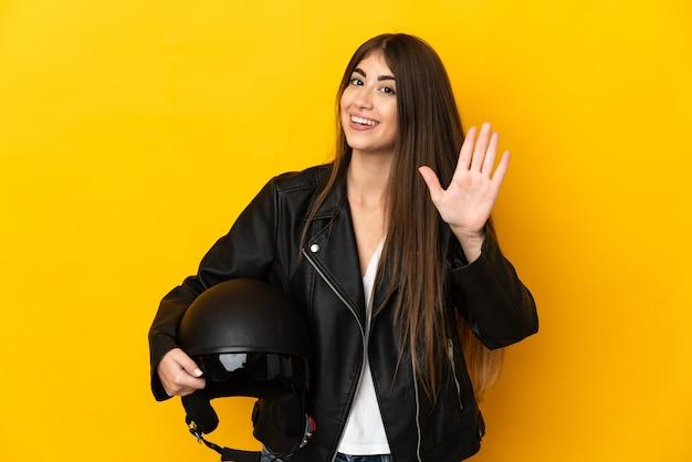 幸せな表情で手で敬礼黄色の壁に分離されたオートバイのヘルメットを保持している若い女性