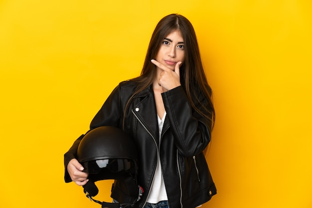 思考黄色の壁に分離されたオートバイのヘルメットを保持している