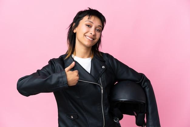 Молодая женщина, держащая мотоциклетный шлем над изолированной розовой, давая недурно жест