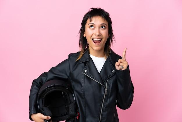 Молодая женщина, держащая мотоциклетный шлем, над розовым указательным пальцем, отличная идея
