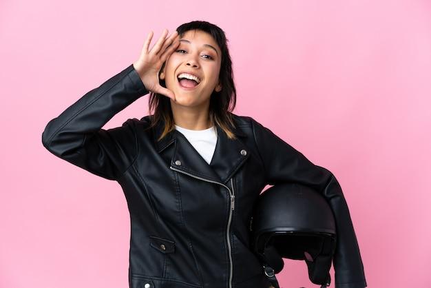 Молодая женщина, держащая мотоциклетный шлем над изолированными розовыми криками с широко открытым ртом