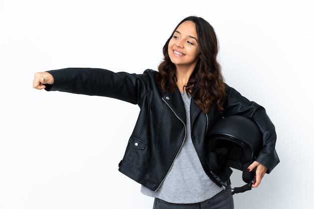 Молодая женщина, держащая мотоциклетный шлем на изолированном белом фоне, жестом показывает палец вверх