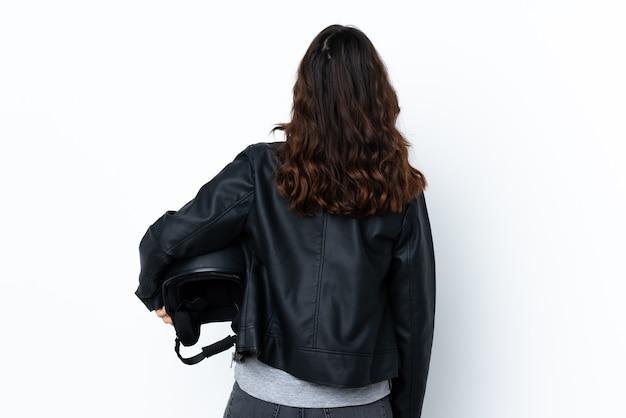 다시 위치에 고립 된 흰색 배경 위에 오토바이 헬멧을 들고 젊은 여자