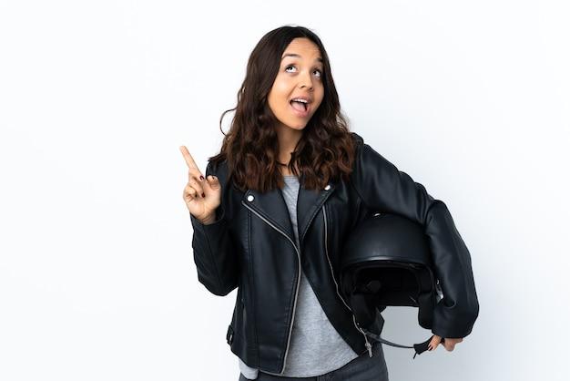 손가락을 들어 올리는 동안 솔루션을 실현하려는 격리 된 흰색 배경 위에 오토바이 헬멧을 들고 젊은 여자