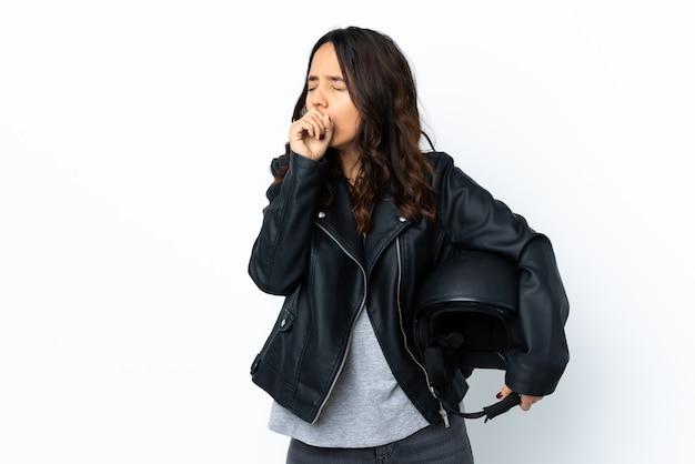 격리 된 흰색 배경 위에 오토바이 헬멧을 들고 젊은 여자는 기침으로 고통 받고 나쁜 느낌
