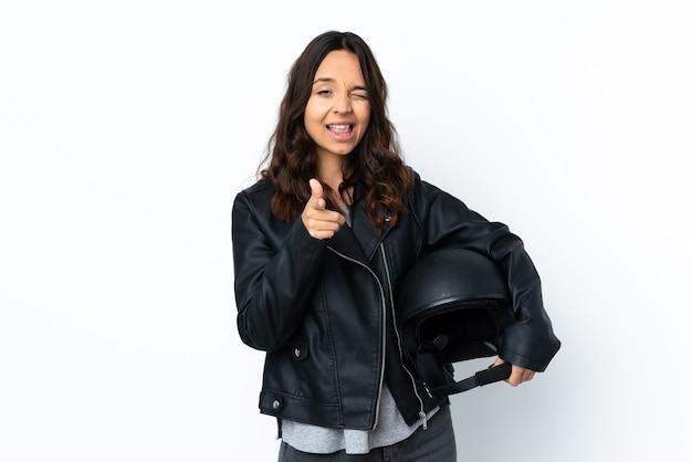 正面を指して笑顔の孤立した白い背景の上にオートバイのヘルメットを保持している若い女性