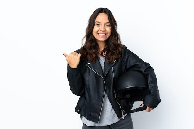 제품을 제시하기 위해 측면을 가리키는 격리 된 흰색 배경 위에 오토바이 헬멧을 들고 젊은 여자