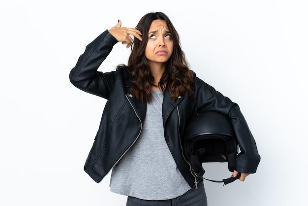 自殺ジェスチャーを作る問題で孤立した白い背景の上にオートバイのヘルメットを保持している若い女性