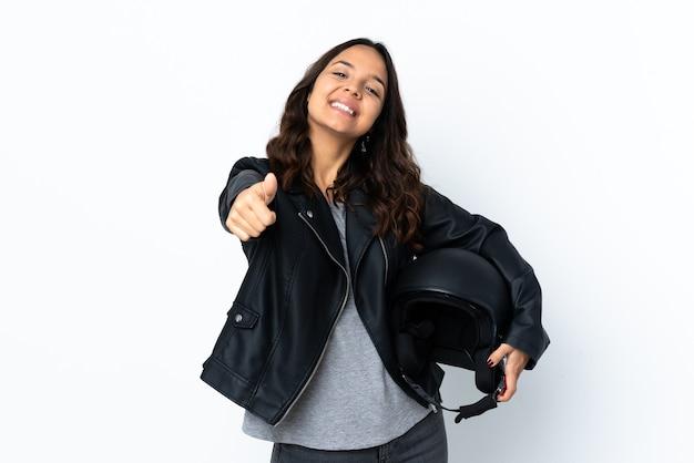 Молодая женщина, держащая мотоциклетный шлем на изолированном белом фоне с большими пальцами руки вверх, потому что произошло что-то хорошее