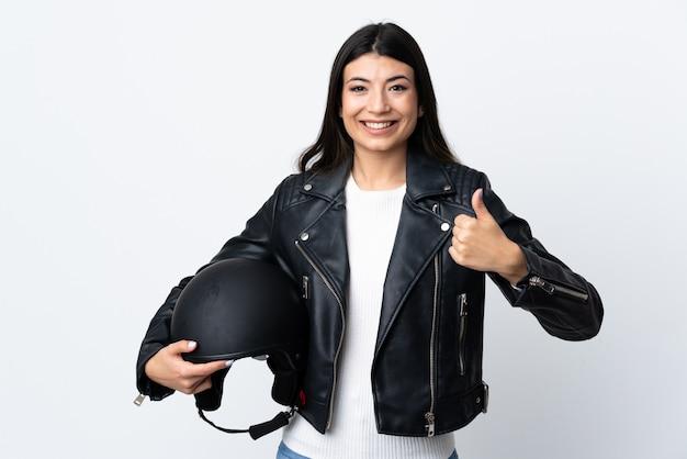 分離された白で親指のジェスチャーを与えるオートバイのヘルメットを保持している若い女性