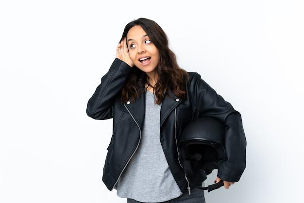 耳に手を置いて何かを聞いて孤立した白の上にオートバイのヘルメットを保持している若い女性