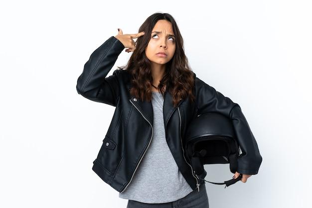 頭に指を置く狂気のジェスチャーを作る孤立した白の上にオートバイのヘルメットを保持している若い女性