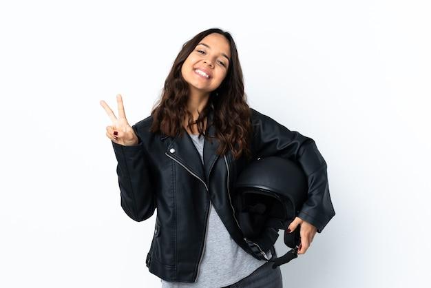 両手で勝利のサインを示す孤立した白の上にオートバイのヘルメットを保持している若い女性
