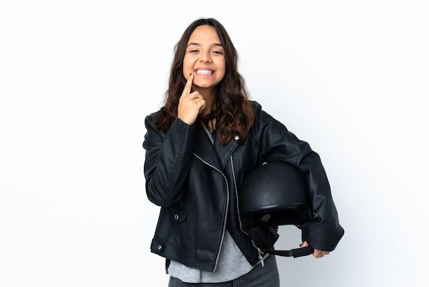 幸せで楽しい表情で笑顔の孤立した白い上にオートバイのヘルメットを保持している若い女性