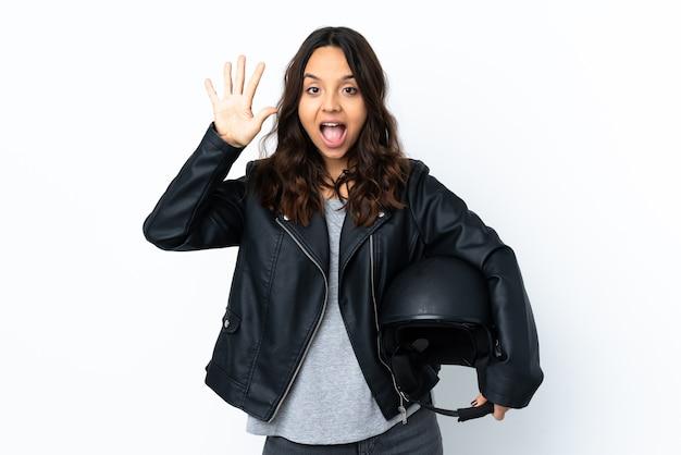 손가락으로 5 세 격리 된 흰 벽 위에 오토바이 헬멧을 들고 젊은 여자