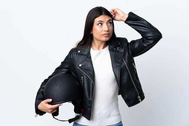 Молодая женщина, держащая мотоциклетный шлем над изолированной белой стеной с сомнениями и с выражением лица путать