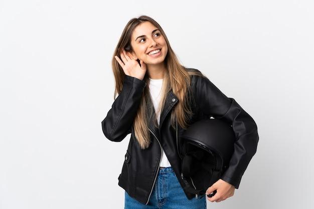 何かを聞いて孤立した白い壁にオートバイのヘルメットを保持している若い女性
