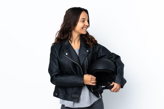 側面を見て孤立した白い壁にオートバイのヘルメットを保持している若い女性