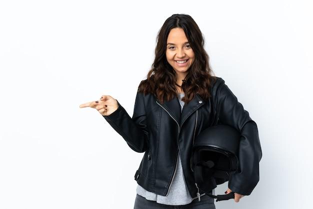 側面に指を指し、幸せな孤立した白い壁にオートバイのヘルメットを保持している若い女性