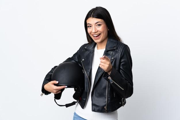 分離の白い壁にオートバイのヘルメットをかざす若い女性が指を指す