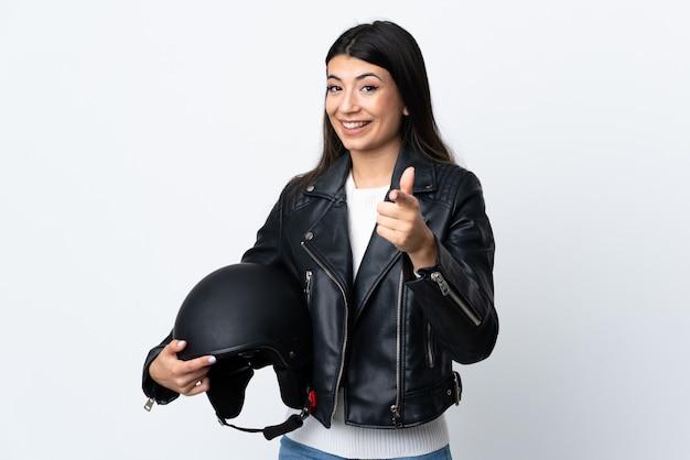 Молодая женщина, держащая мотоциклетный шлем над белой стеной, указывает пальцем на тебя