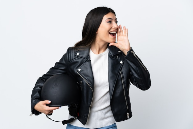 Молодая женщина, держащая мотоциклетный шлем над изолированной белой стеной, крича с широко открытым ртом