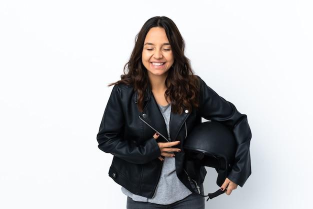 たくさん笑って孤立した白い壁にオートバイのヘルメットを保持している若い女性