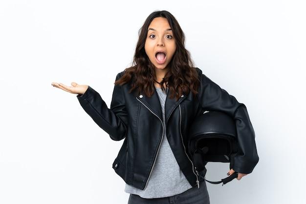 Молодая женщина, держащая мотоциклетный шлем над изолированной белой стеной с шокированным выражением лица