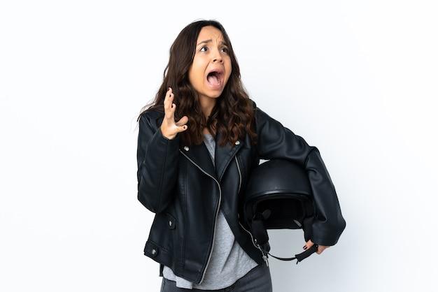 驚きの表情で孤立した白い壁にオートバイのヘルメットを保持している若い女性