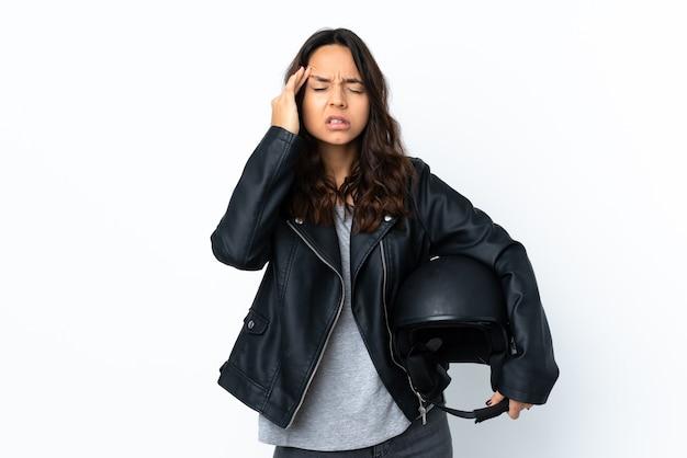 頭痛と孤立した白の上にオートバイのヘルメットを保持している若い女性