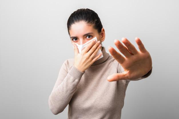 Молодая женщина держит салфетку от вируса и поднимает руку