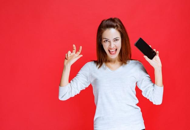 Молодая женщина держит новую модель черного смартфона и чувствует себя позитивно и удовлетворенной