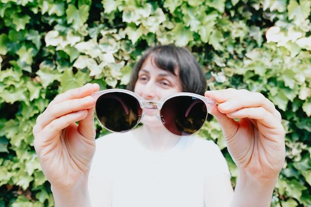 笑顔、夏のコンセプトのカメラにサングラスを保持している若い女性