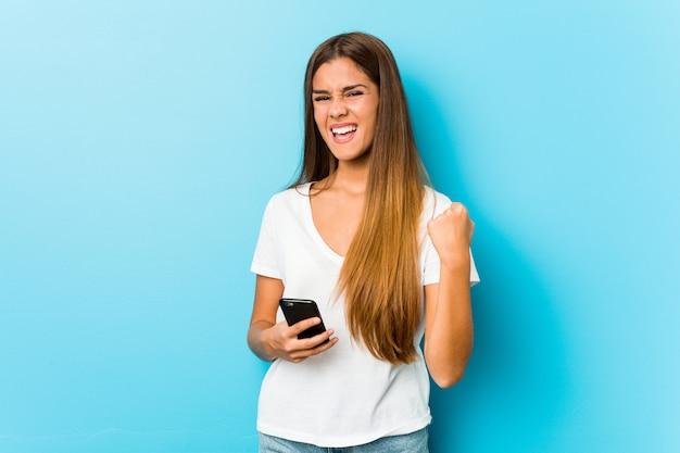 屈託のない、興奮した電話を保持している若い女性