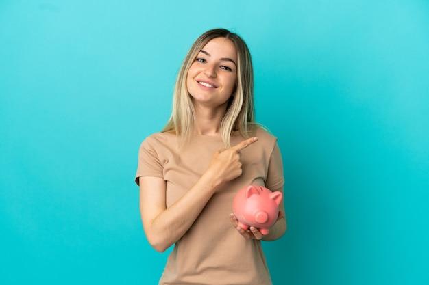 제품을 제시하기 위해 측면을 가리키는 고립된 파란색 배경 위에 돼지 저금통을 들고 있는 젊은 여성