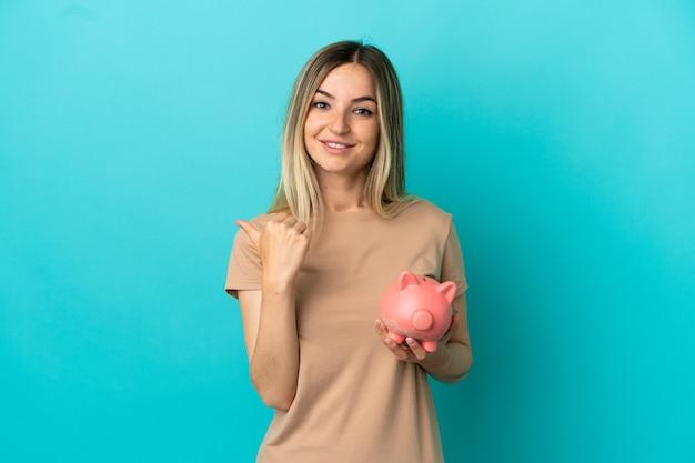 Молодая женщина, держащая копилку на синем фоне, указывая в сторону, чтобы представить продукт