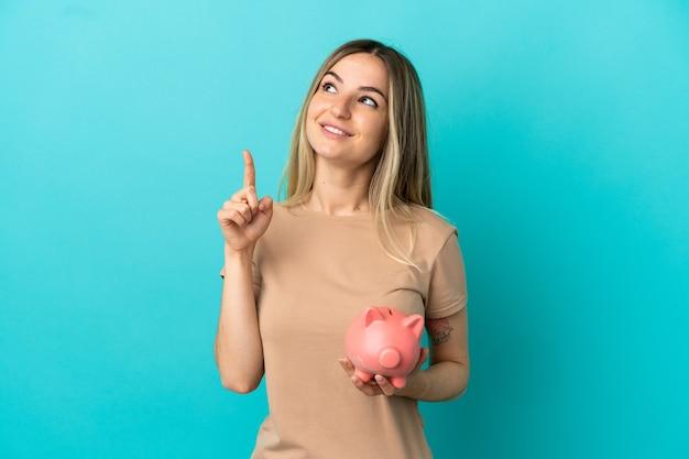 멋진 아이디어를 가리키는 고립된 파란색 배경 위에 돼지 저금통을 들고 있는 젊은 여성