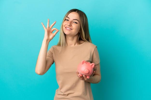 손가락으로 확인 표시를 보여주는 고립 된 파란색 배경 위에 돼지 저금통을 들고 젊은 여자