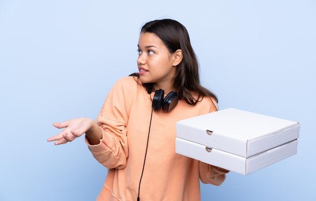 驚きの表情で青い壁にピザを置く若い女性