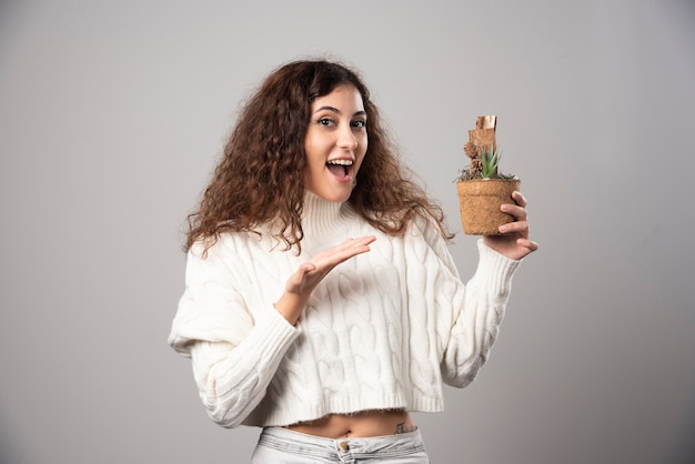 식물을 잡고 그것을 가리키는 젊은 여자. 고품질 사진