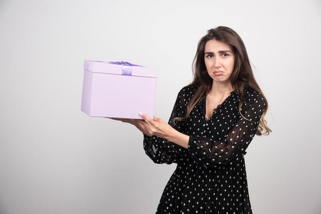보라색 선물 상자를 들고 젊은 여자
