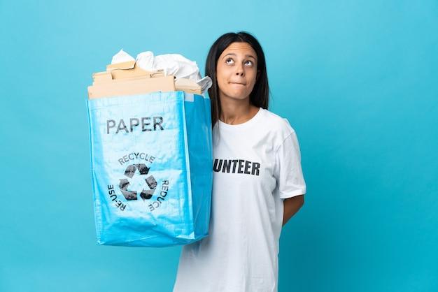 紙でいっぱいのリサイクルバッグを持って見上げる若い女性