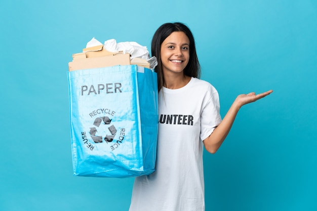 紙でいっぱいのリサイクルバッグを持って、手を横に伸ばして招待する若い女性