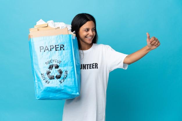 親指を立てるジェスチャーを与える紙でいっぱいのリサイクルバッグを保持している若い女性