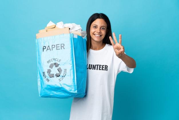 幸せな紙でいっぱいのリサイクルバッグを持って、指で3を数える若い女性