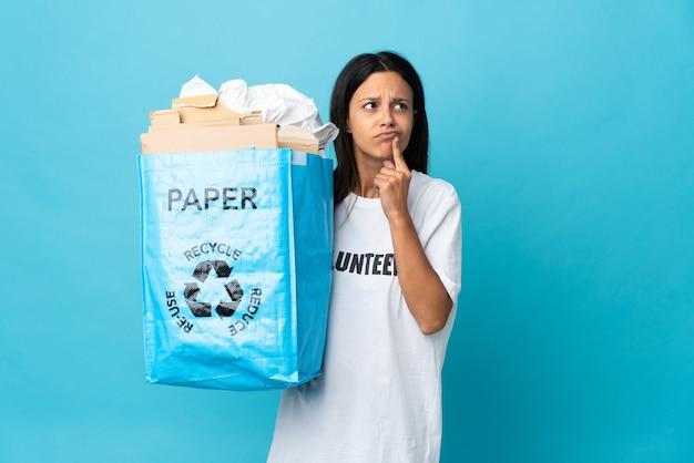 見上げながら疑問を持っている紙でいっぱいのリサイクルバッグを保持している若い女性